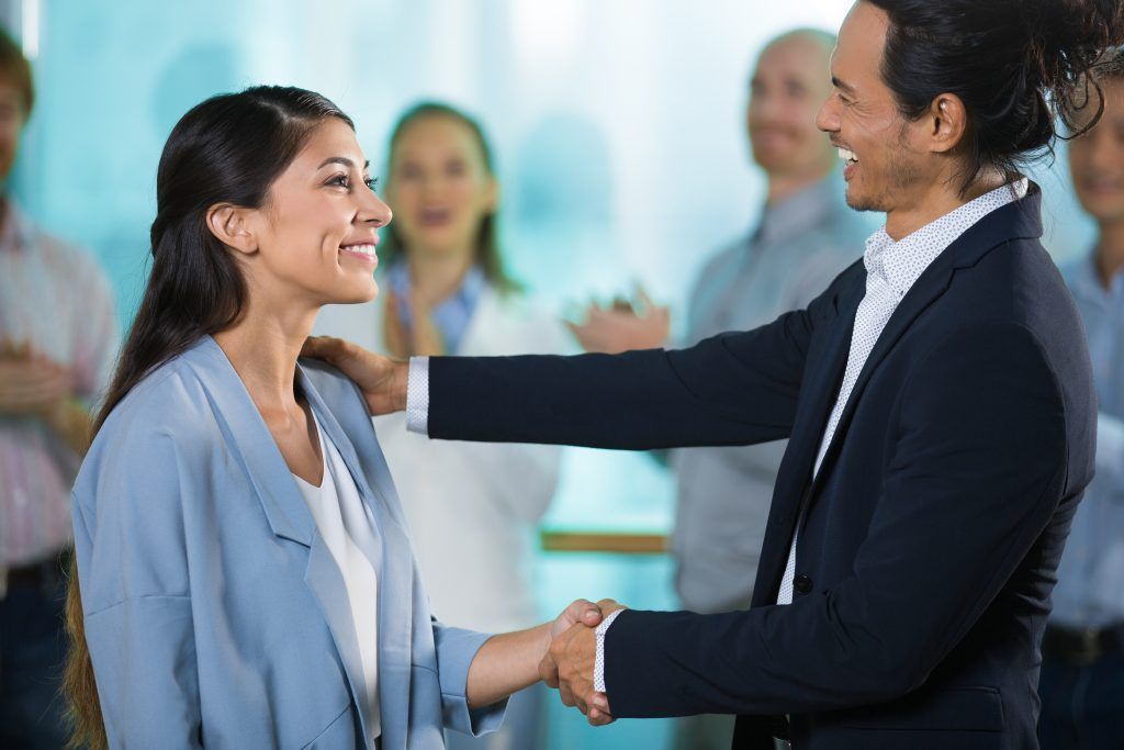 Happy boss greeting new female manager and shaking hands. Smiling young woman listening to speech of mentor at meeting. Business people applauding in background. Best worker concept